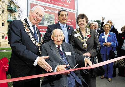 Wilts and Gloucestershire Standard: Sir Bernard Lovell cuts the tape to open the road named after him, watched by parish council chairman Ian Henderson, Redrow Homes' Peter Carpinelli, Mayor Catherine Doody and former workers at the Ekco factory