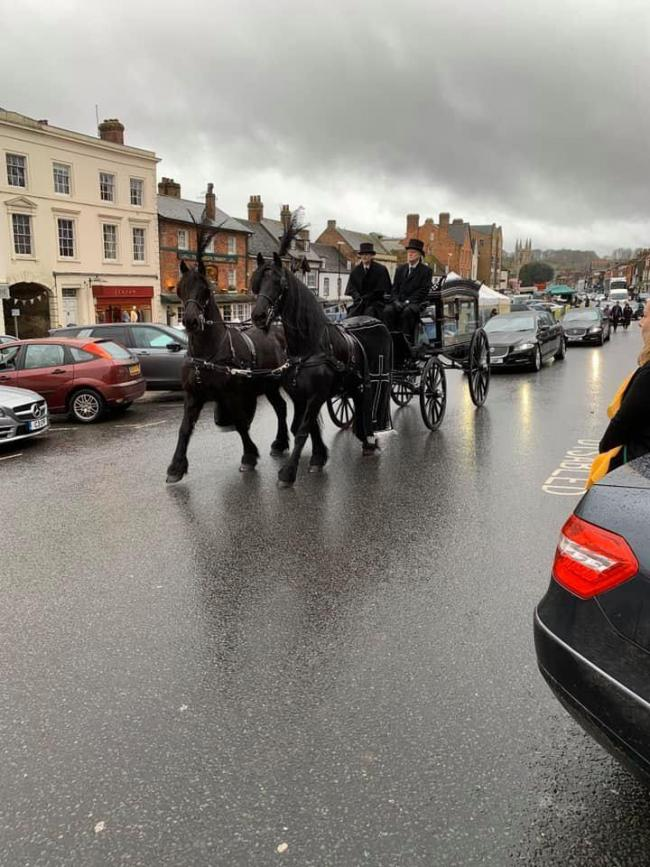 Black horses carry the coffin of jockey James Banks along Marlborough High Street