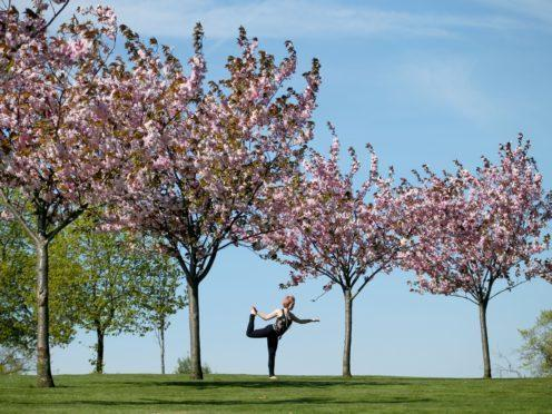 Yoga is a great way to stay fit during the lock down – just do it in your living room and not in the park (Jane Barlow/PA)