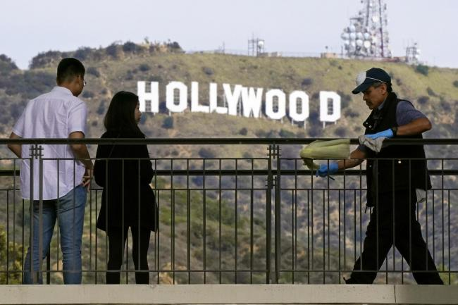 Pedestrians look at the Hollywood sign as a worker cleans the rails at Hollywood & Highland in Los Angeles