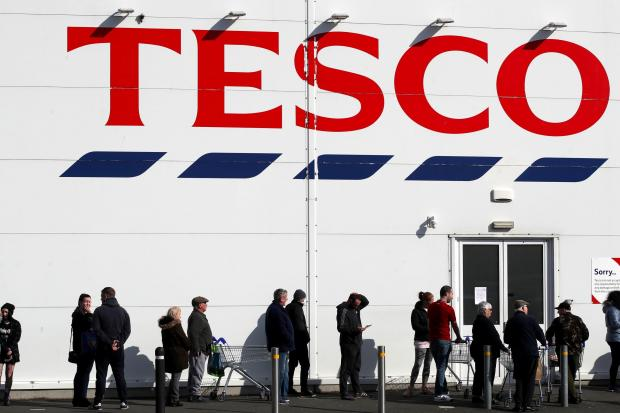 Wilts and Gloucestershire Standard: People queue outside a Tesco Extra store in Madeley, Shropshire