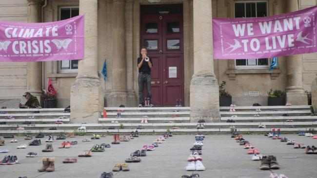 Extinction Rebellion installation of childrens shoes