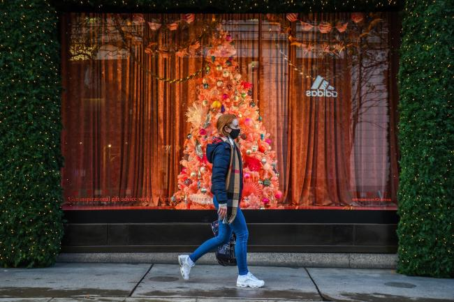 A woman wearing a face mask passes a Christmas window display on Oxford Street, London