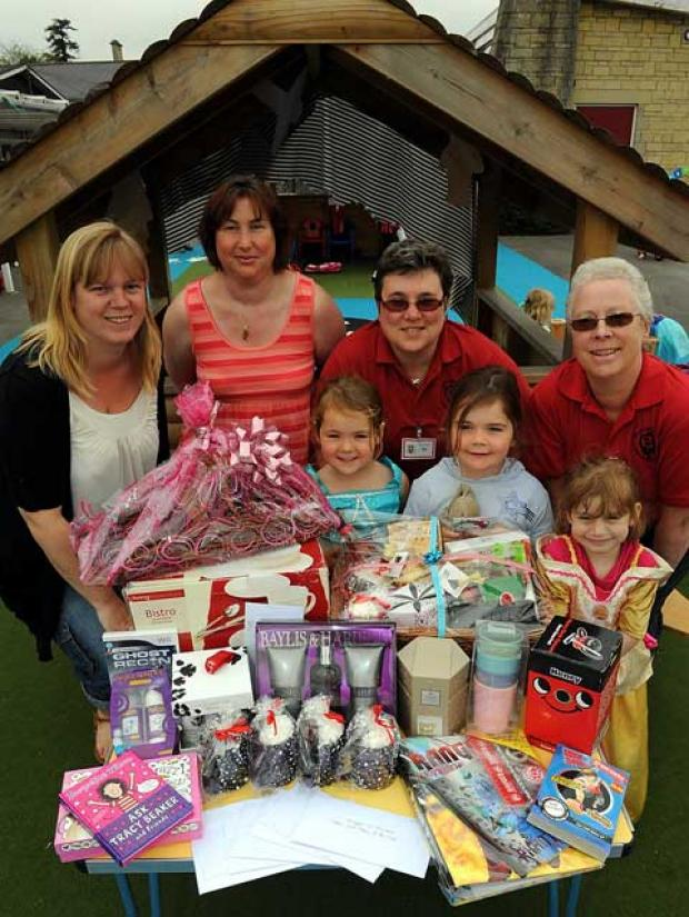 Kelly Motti, Sharon Woodruffe, Di Abonyi and Hilary Lawrence with children Kesia, Enya and Hannah and some of the items to raise money for Lewis Lane Playgroup