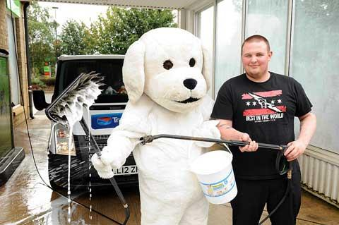 Store manager Rob Parnell sporting a dog costume during the fundraising car wash to raise money for guide dogs. Also pictured is staff member Robert Evans at the Burford Road garage in Cirencester