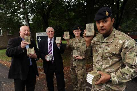 Corporal Nacanieli Taukei holds one of the new Gideons bibles watched by Rev David Bowers, Dennis Hill and Captain Branwen Jones at the 29th Regiment at South Cerney