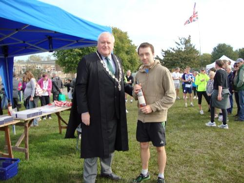 Cricklade 10k winner Miles Thomas, from Lliswerry Runners, receives his trophy from Cricklade Court Leet's High Bailiff Clive Smith