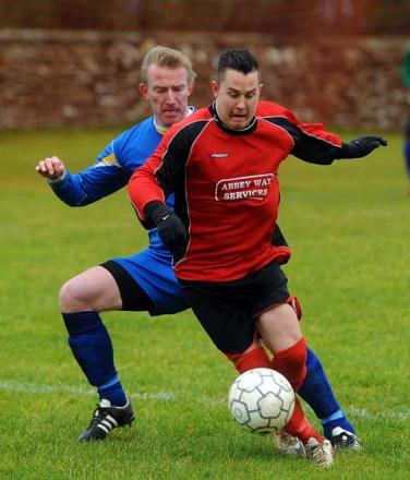 Darren Parker of Bibury (red) tussles in the Star FC clash