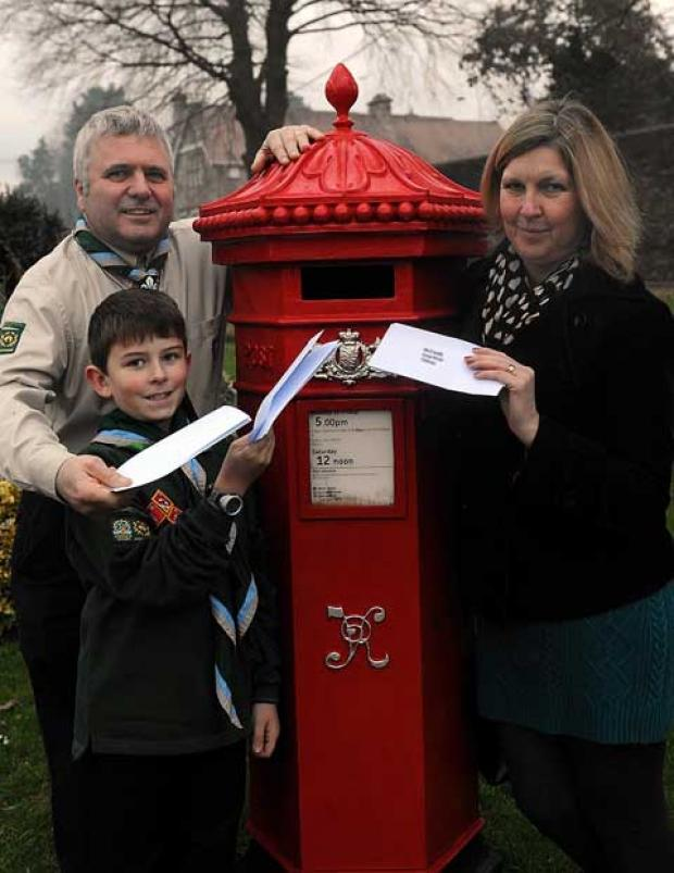 Peter and Eileen Hodgson with Scout Joe Elshaw, nine, in Tetbury