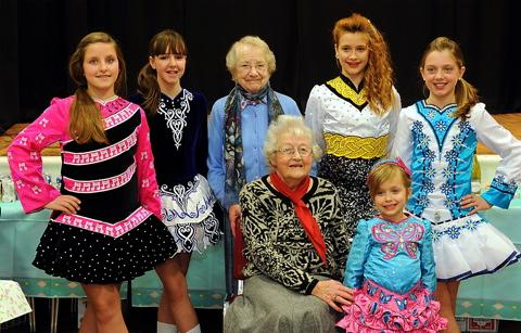 Pensioners Joan Braithwaite and Mary Poole meet dancers from the Clare Farrell School of Irish Dance who provided entertainment at the party held at the Palmer Hall in Fairford