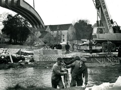 The new pedestrian bridge being swung into place across the River Coln in Bibury