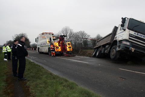 Recovery teams drag the lorry back out of the ditch on the A429 this afternoon.
