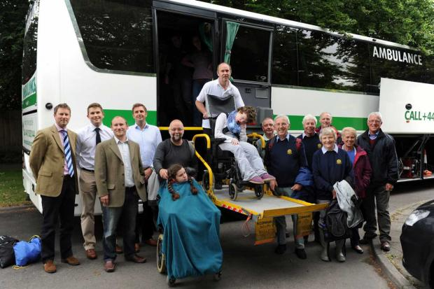 Members of the Cirencester Round Table and Rotary Club by the Jumbulance to take pupils from Paternoster school for a trip to Westonbirt Arboretum