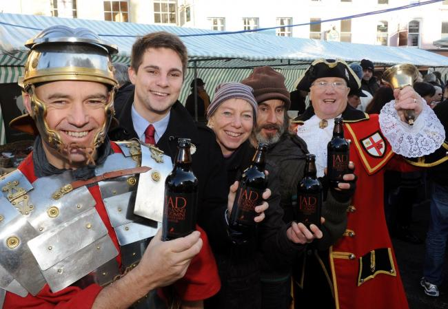 Roman legionary Steve Manning, Cirencester Mayor Joe Harris, Lucy Cordery and Colin Knight from Corinium Ales and town crier Tony Evans holding bottles of the anniversary ale last year