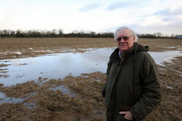 Cllr Ray Theodoulou, who is also against the plans, standing on the land where the homes will be built