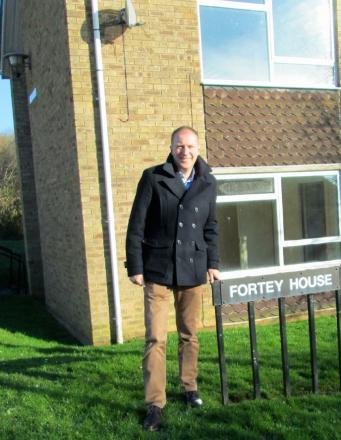 Cllr Paul Hodgkinson standing in front of Fortey House in Northleach