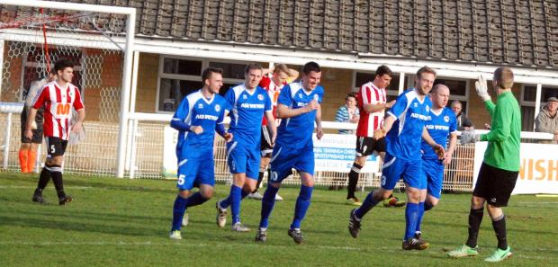 Fairford Town (in their blue away strip) celebrate one of their equalisers at Shortwood United
