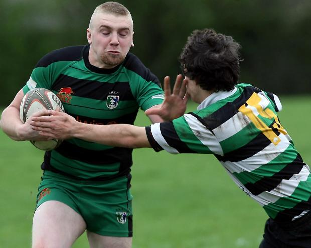 Wilts and Gloucestershire Standard: Fairford try scorer Mike Wrona hands off young Minch full back Jack Richards