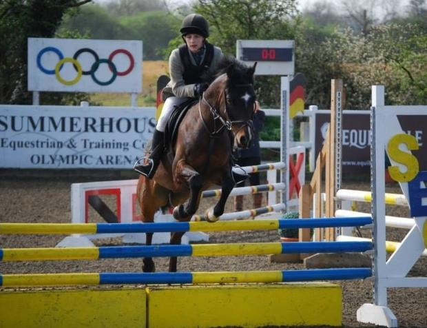 Eliza Gibb of Malmesbury School in show jumping action on Pusey