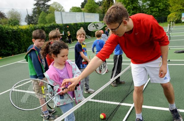 Wilts and Gloucestershire Standard: Coach Floyd Magson helps Olina Young, 5, with her grip at the touchtennis session held in St Michael's Park, Cirencester. Picture: Richard Pasco  (6101924)