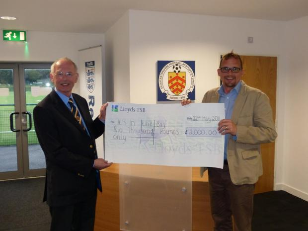 Gloucestershire FA chairman Roger Burden (left) presenting a cheque for £2,000 to It's in the Bag representative Jon Baker