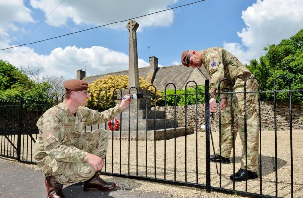 Corporal Jacko (right) and Trooper H paint the Poulton war memorial railings in time for the commemorations this August