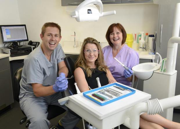 Dr Cutts prepares to give NatWest's Jennifer Scott's teeth a check over, accompanied by dental nurse Susanne Sloper