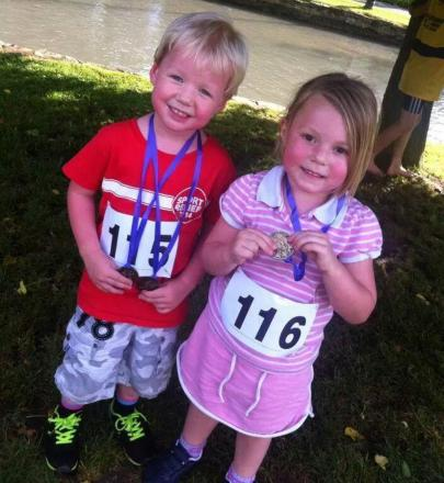 Twins Robbie and Daisy Reeve (Bourton Roadrunners' future stars) proudly display their fun run medals. Picture by Claire Harrison.