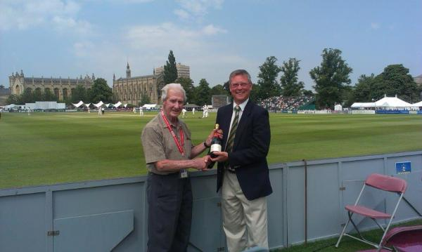Eric Gordon being presented with a bottle of champagne by Paul Nurden - divisional director of Brewin Dolphin, the Cheltenham Festival's principal sponsors