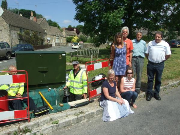 BACK L:R - Estelle Collett, Mike Edwards, Elmore Crump and Phillip Walter and at the front Linda De Carles (left) and Sam Frost by the broadband box on the Village Green