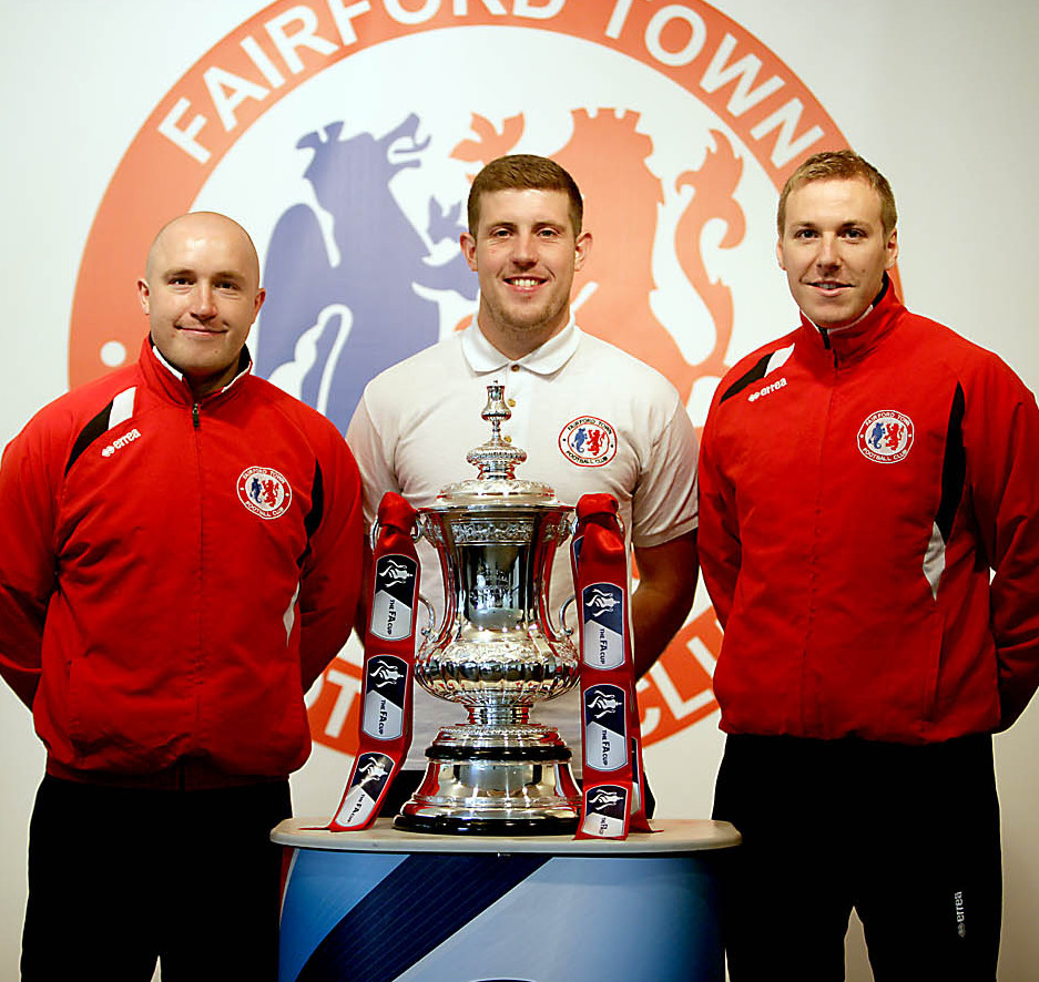 Fairford Town players pose with the FA Cup at their Cinder Lane ground on Saturday. Left to right: defenders Colin Curtis and Alex Evans alongside striker Alex Rudd (9373943)