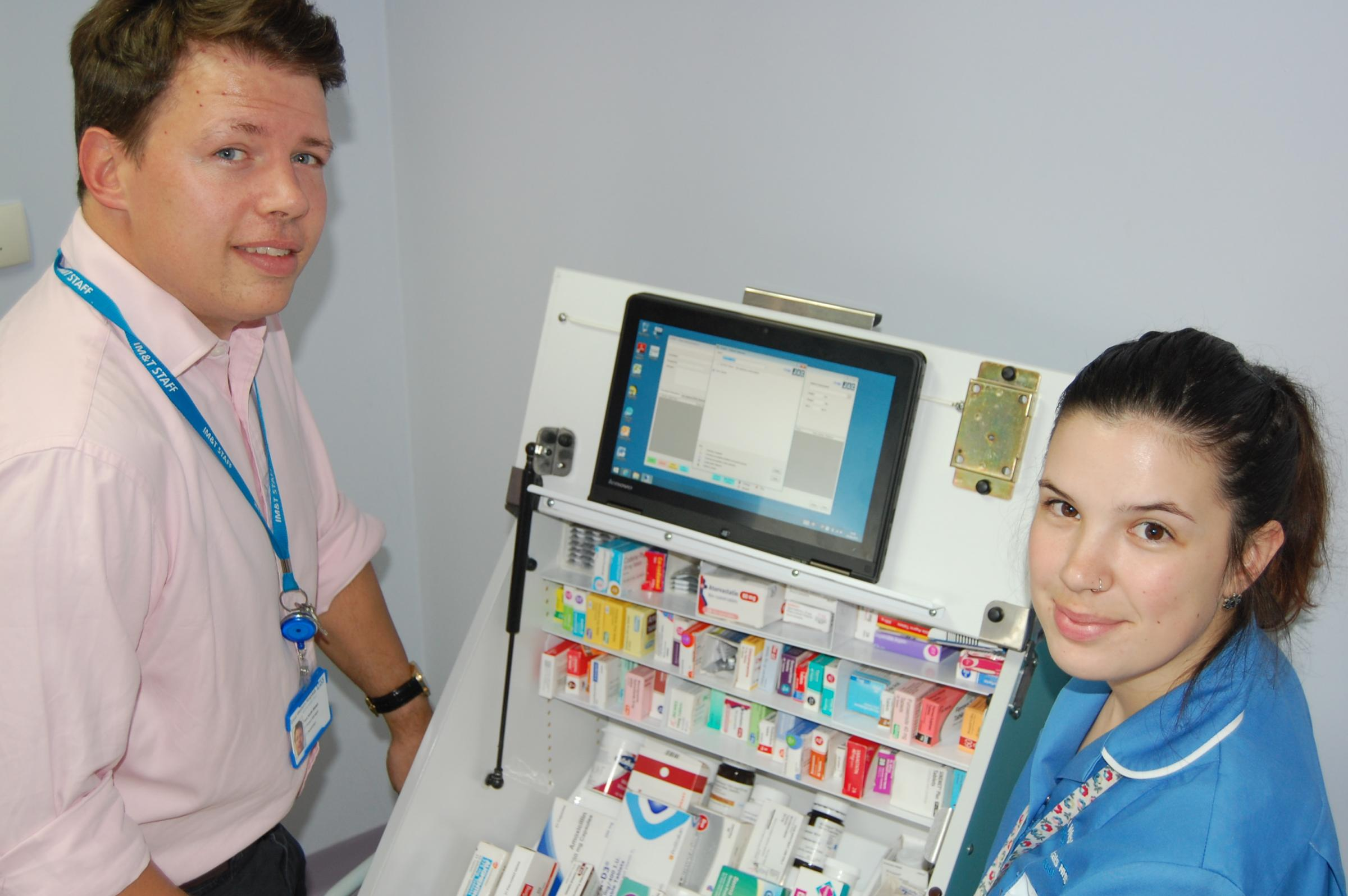 Tom Keith-Welsh, Great Western Hospitals NHS Foundation Trust's EPMA Project Manager with Falcon Ward Staff Nurse Sonia Soares, next to a medicine trolley and an EPMA portable computer