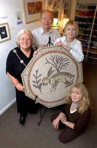 Cirencester mayor Shirley Alexander and Richard Kent, chairman of the Twinning Association, take possession of the hare mosaic from artists Anya Burzec and Debbie Stirling at Number Nine in Silver Street