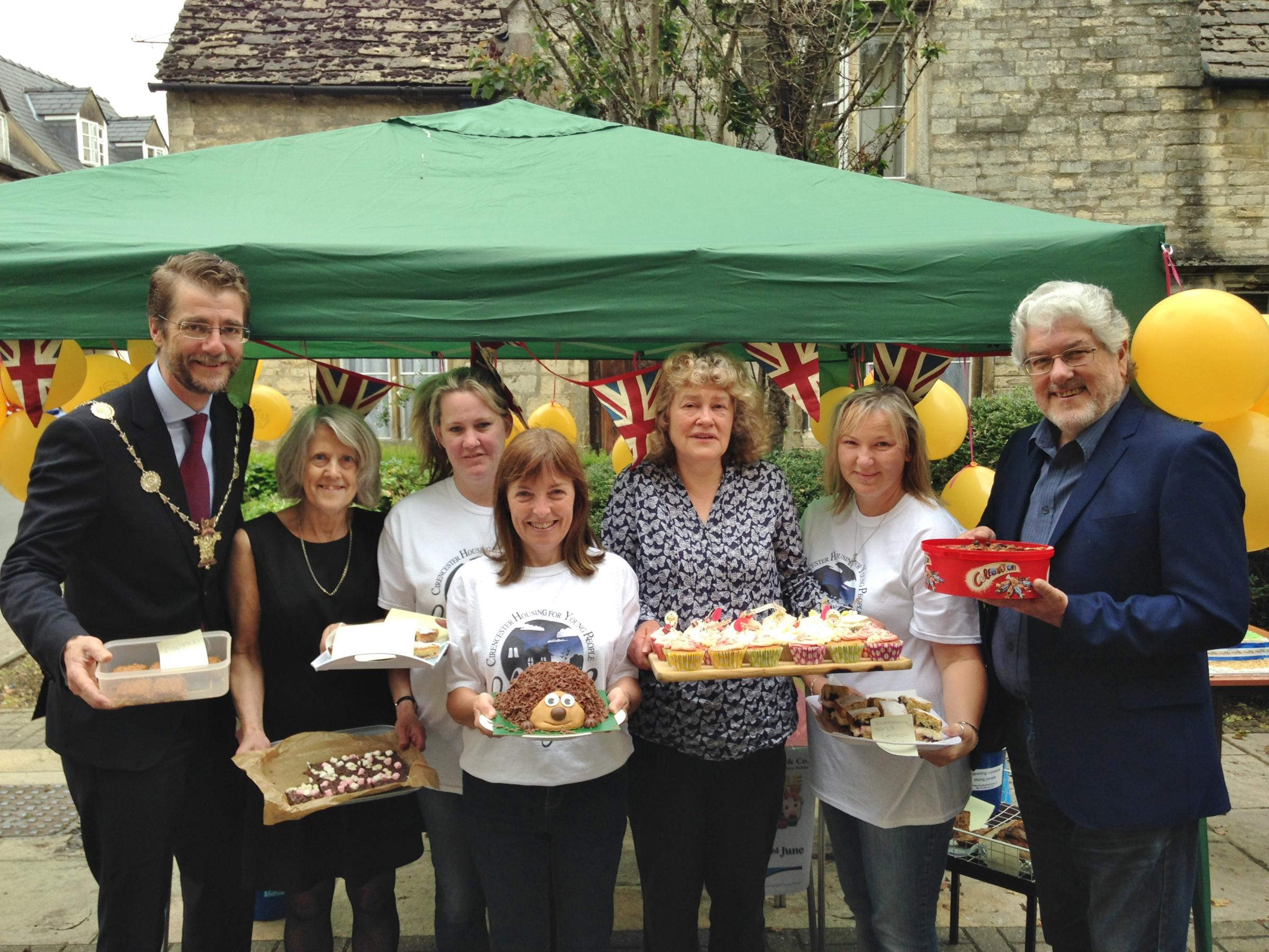 Cirencester mayor Mark Harris (left) with Alison Fielden (second left) and Andy Johnson (right) with volunteers from CHYP at the fundraising cake sale