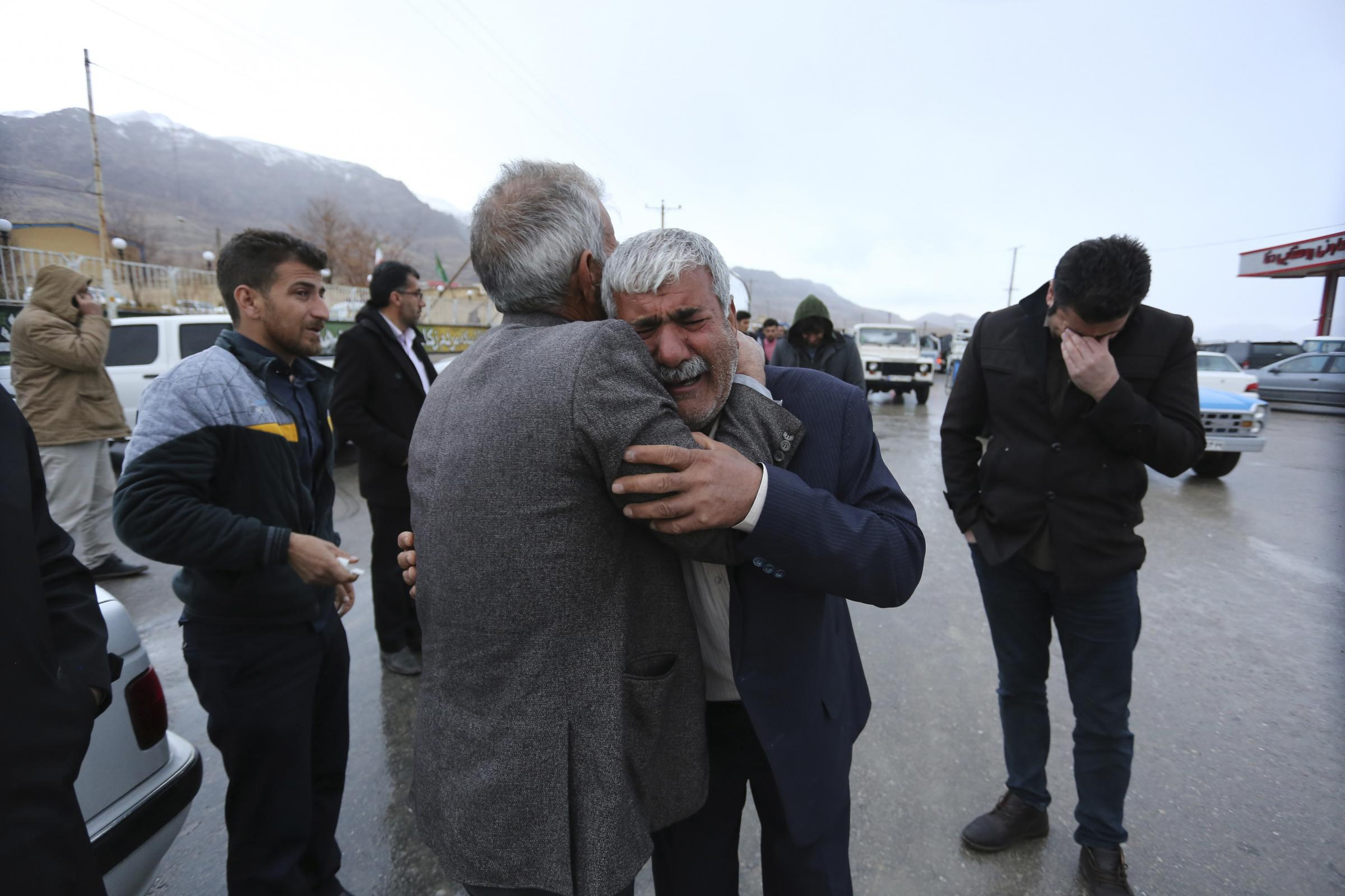 Family members of plane crash victims weep in the village of Bideh, at the area that the plane crashed, southern Iran (Ali Khodaei/Tasnim News Agency via AP)