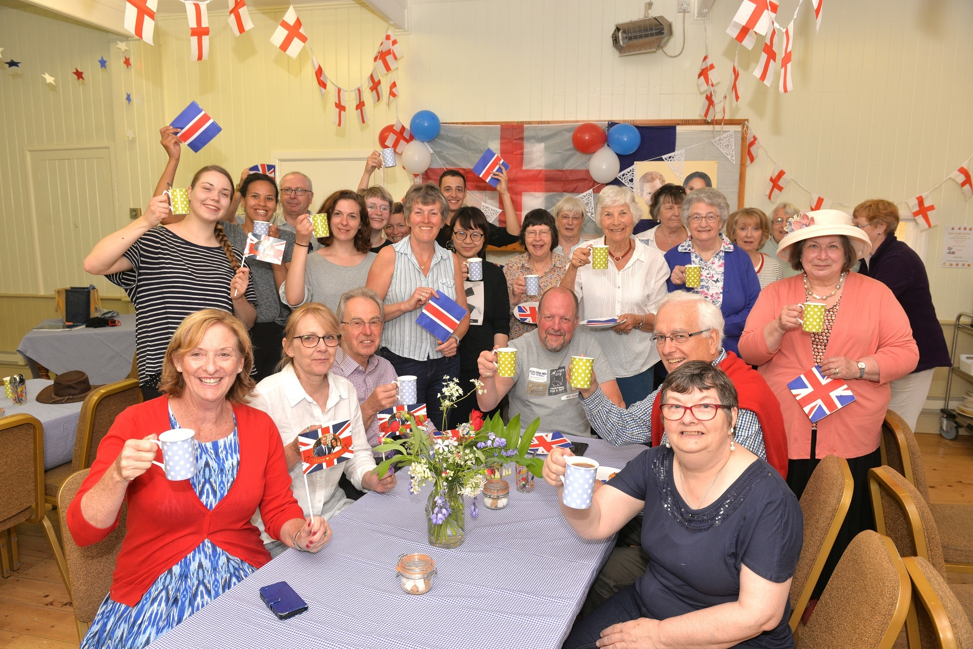 Residents of Coates, visitors and Coates Kitchen volunteers raise a toast during their Royal Wedding Coffee morning at Coates Village Hall