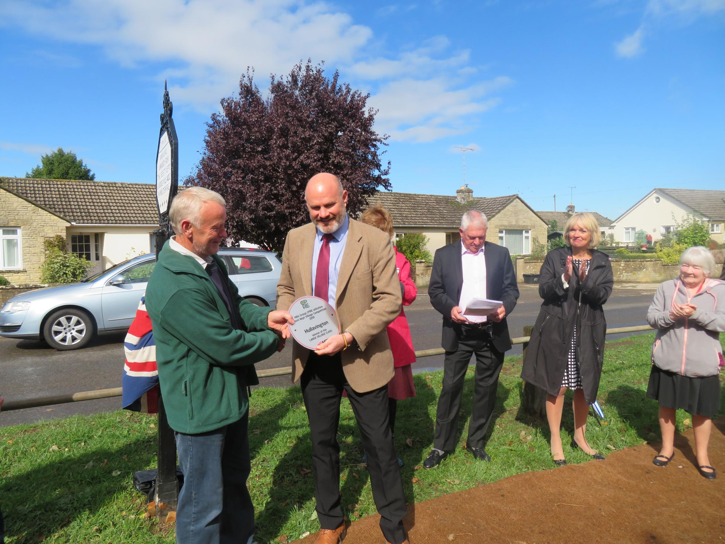 Mike Hill, Chief Executive of The Hills Group, presents their plaque to volunteer odd job man and parish councillor Hank Slater