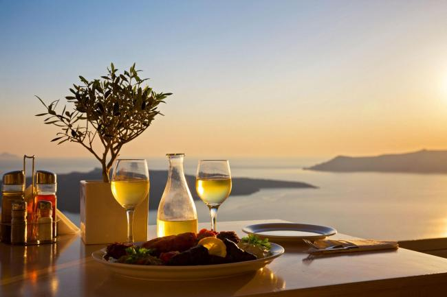 A Generic Photo of romantic table for two with sea and volcano in background, Santorini, Greece. See PA Feature TOPICAL Drink Volcanic. Picture credit should read: PA Photo/iStock. WARNING: This picture must only be used to accompany PA Feature TOPICAL Dr
