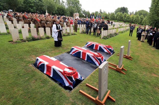 The coffins of two young privates and an unknown soldier, who fought during the First World War, during a burial service at Hermies Hill British Cemetery near Albert, France